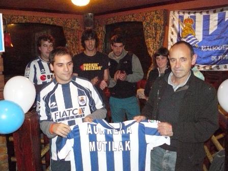 Luis, el presidente de la peña Aurrera Mutilak, recibe la camiseta de la Real Sociedad que le entrega el consejero Juanjo Bueno.