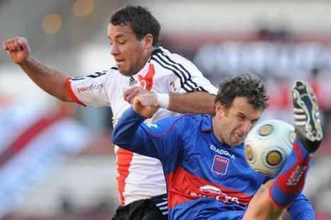 Arruabarrena intenta controlar un balon ante la presion de un jugador del River