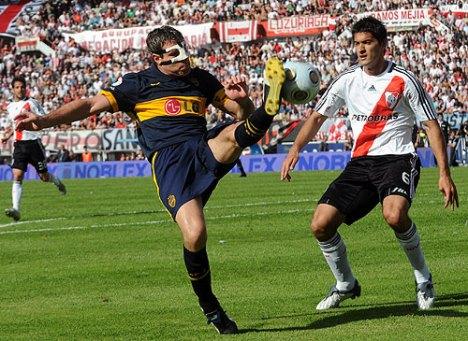 Palermo lucha un balon ante Sanchez ( River)