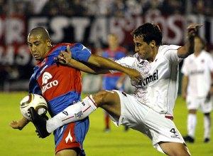 el Chino Luna lucha por un balon ante un defensor del Newell,s